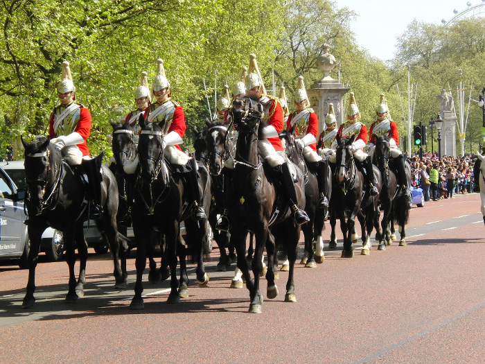 Soldiers riding horses through London in ceremonial dress